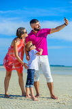 Family of three running along the tropical beach, laughing and enjoing time together. Stock Images