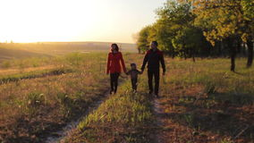 Happy family of three walking at sunset near a forest. stock footage