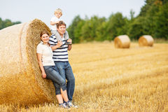 Happy family of three on yellow hay field in summer. Stock Image