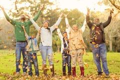Happy family throwing leaves around Stock Photo