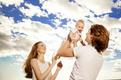 Happy family throws up baby boy against blue sky Stock Photos