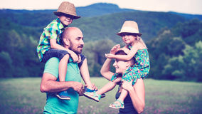 Happy family time concept. Parents giving piggyback ride to children, happy family time concept stock photography