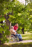Happy family time- elderly man in wheelchair talking with daught. Happy family time- Smiling elderly men in wheelchair talking with daughter in the park Stock Image