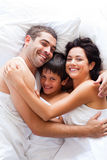 Happy family together in bed Stock Photography