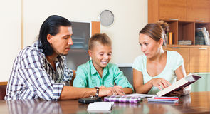 Happy family together doing homework Stock Photography