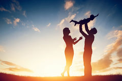 Happy family together, parents with their little child at sunset. Father raising baby up in the air Stock Photography