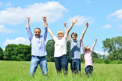 Happy family together raising their arms. Cheerful family of four lifting arms up in the air Stock Photos