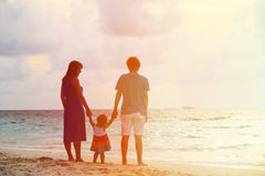 Happy family together at sunset beach Stock Photo