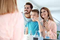 Happy family with toothbrushes near mirror in bathroom. stock image