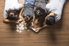 Happy family top view lying on floor with jigsaw puzzle