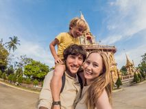 A happy family of tourists on the background of Wat Chalong in Thailand. Traveling with children concept stock photos