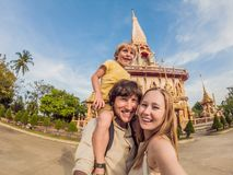 A happy family of tourists on the background of Wat Chalong in Thailand. Traveling with children concept stock photo
