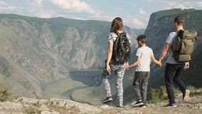Happy family of tourists come to the peak of the mountain and rejoice raising their hands up. Happy young family of tourists with a child approach the peak of stock video footage