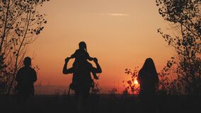 Happy family tourists go hiking in park sunset silhouette. Adventure travel concept. Teamwork. happy family a tourists