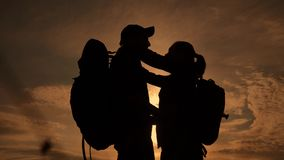 Happy family tourists silhouette at sunset hug kissing. teamwork travel concept. man and woman couple with backpacks. Happy family tourists silhouette sunset hug stock video