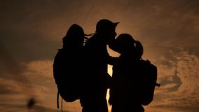 Happy family tourists silhouette at sunset hug kissing. teamwork travel concept. man and woman couple lifestyle with stock video
