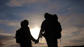 Happy family tourists walking holding hand lifestyle silhouette at sunset. hikers teamwork travel concept. man and woman. Couple with backpacks tourists stock video footage