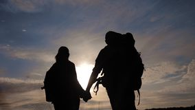 Happy family tourists walking holding hand silhouette at sunset . hikers teamwork travel concept. man lifestyle and. Woman couple with backpacks tourists stock footage