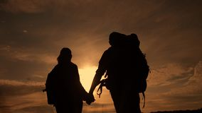 Happy family tourists walking holding hand silhouette at sunset . hikers teamwork travel concept. man and lifestyle stock video