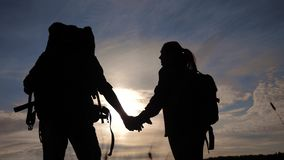 Happy family tourists walking holding hand silhouette at sunset . hikers teamwork travel concept. man and woman couple. With backpacks tourists adventure stock footage