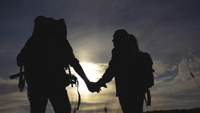 Happy family tourists walking holding hand silhouette at sunset . hikers teamwork travel concept. man and woman couple. With backpacks tourists lifestyle stock footage
