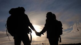 Happy family tourists walking holding hand silhouette at sunset. Hikers teamwork travel concept. Man and woman couple stock video