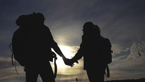 Happy family tourists walking holding hand silhouette at sunset . hikers teamwork travel concept. man and woman stock video footage