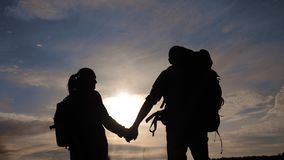 Happy family tourists walking holding hand silhouette at sunset . hikers teamwork travel lifestyle concept. man and stock footage