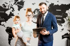 Happy family with travel agent at the office. Happy mother and baby boy choosing tour for a summer vacation with male agent at the travel agency office with Stock Image