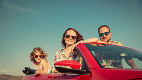 Happy family travel by car in the mountains. People having fun in red cabriolet. Summer vacation concept Stock Photography