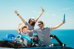 Happy family travel by car to the sea. People having fun in cabriolet. Summer vacation concept royalty free stock image