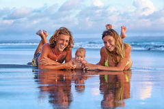 Happy family travel - father, mother, baby son on sunset beach Royalty Free Stock Image