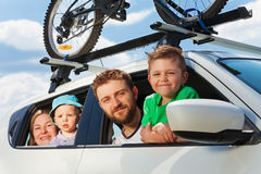 Happy family traveling by car on summer vacation. Happy family, parents with two age-diverse sons, looking out the window of car during summer trip Stock Images