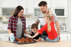 Happy family with tray of oven baked buns royalty free stock photo