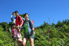 Happy family on a trekking day. Family on a hiking day going down hill Stock Images