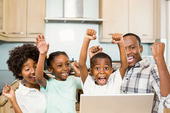 Happy family triumphing in the kitchen Royalty Free Stock Images