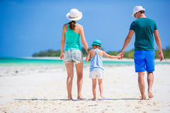 Happy family at tropical beach having fun. Happy family and adorable little daughter at tropical beach having fun Royalty Free Stock Photos