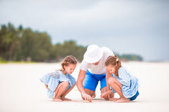 Happy family at tropical beach having fun. Happy father and adorable little daughters at tropical beach having fun Royalty Free Stock Images