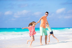 Happy family at tropical beach having fun. Happy father and adorable little daughters at tropical beach having fun Stock Images