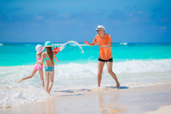Happy family at tropical beach having fun. Happy father and adorable little daughters at tropical beach having fun Stock Image