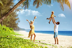 Happy family tropical beach having fun. Happy family of father mother and little son having fun at tropical beach under palm tree Stock Photography