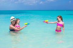 Happy family at tropical beach having fun. Happy mother and little girls at tropical beach having fun Stock Photo