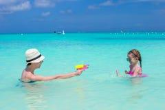 Happy family at tropical beach having fun. Happy mother and little girls at tropical beach having fun Stock Image