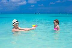 Happy family at tropical beach having fun. Happy mother and little girls at tropical beach having fun Stock Photography