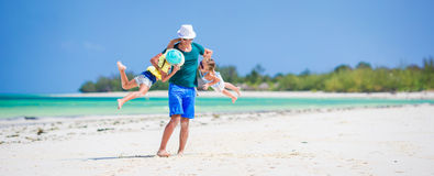 Happy family on tropical beach having fun together. Happy father and adorable little daughters at tropical beach having fun Stock Photos