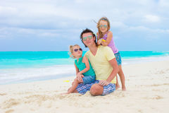 Happy family on tropical beach having fun together. Happy father and adorable little daughters at tropical beach having fun Royalty Free Stock Image