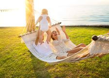 Happy family on a tropical island at sunset lie in a hammock and play with their son.  royalty free stock photography