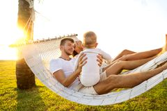 Happy family on a tropical island at sunset lie in a hammock and play with their son.  stock image
