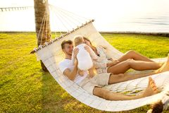 Happy family on a tropical island at sunset lie in a hammock and play with their son.  stock images
