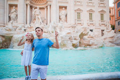 Happy family trowing coins at Trevi Fountain, Rome, for good luck. Little girl and father making a wish to come back. Royalty Free Stock Photography